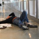 An image of a distressed man with papers around him while he is on the floor after a slip and fall.